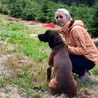 Nadja Bohlig mit Hund im Weihnachtsbaumfeld